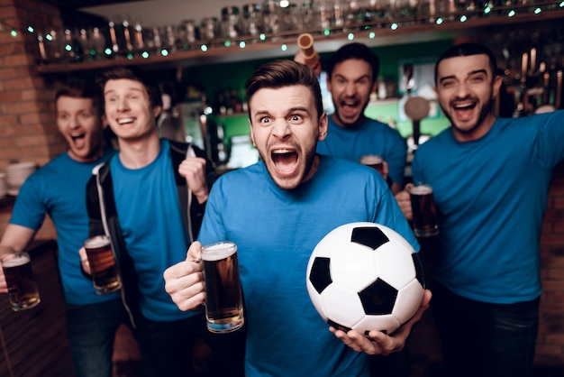 Five soccer fans drinking beer celebrating in bar. Premium Photo
