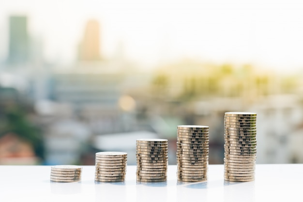 Five stack of coins on city backgrounds. Premium Photo