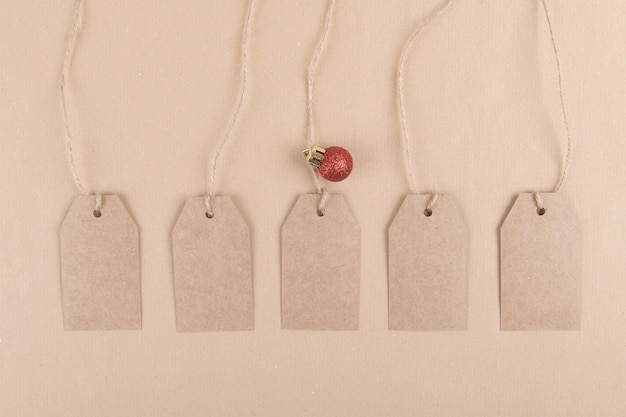 Five tags of recycled kraft paper for packaging hanging from a rope decorated with a red christmas ball Premium Photo