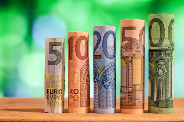 Five, ten, twenty, fifty and one hundred euro rolled bills banknotes on green blurred bokeh Premium Photo
