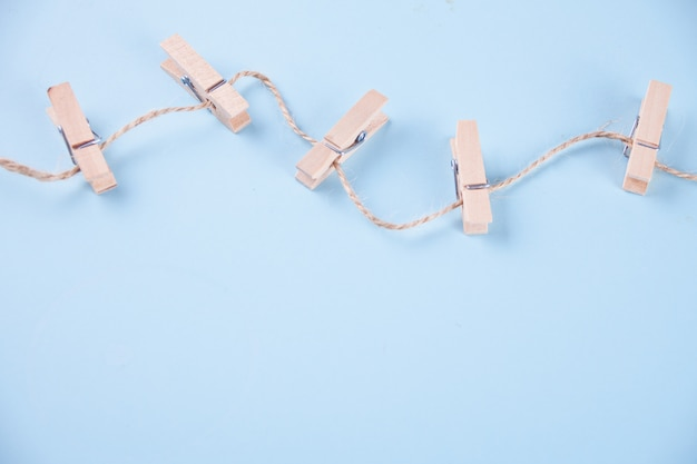 Five wooden clothespins on a rope on blue background Premium Photo