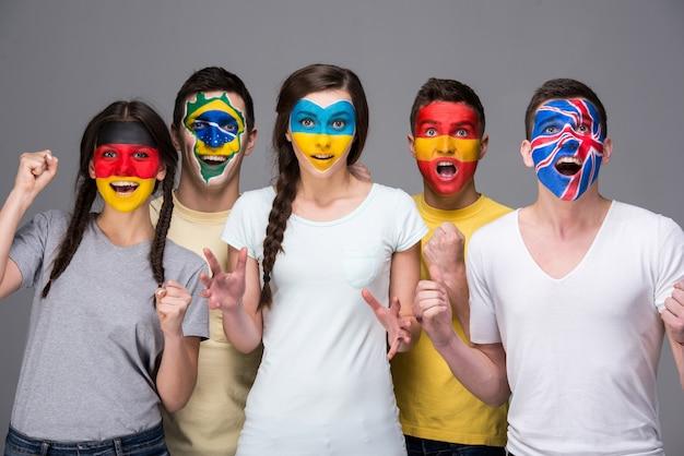 Пятеро молодых людей с государственными флагами нарисованы на лицах. Premium Фотографии