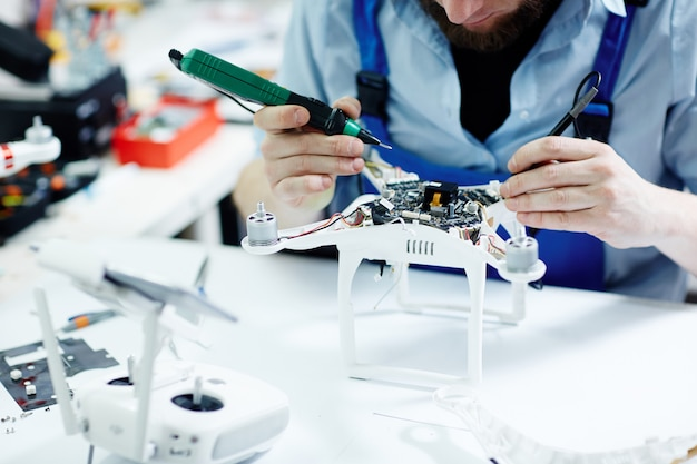 Fixing drone in maintenance shop Free Photo