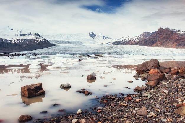 氷山氷河ラグーンfjallsarlon。積雲の白い雲が反射します Premium写真