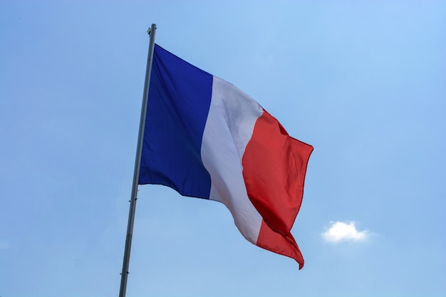 Flag of france against a blue sky with clouds Premium Photo