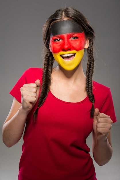 Flag of germany painted on a face of young woman. Premium Photo