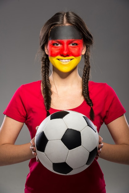 Flag of germany painted on a face of a young woman. Premium Photo