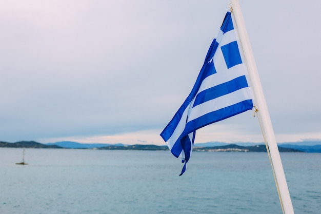 Flag of greece on the ship against the cloudy sky Premium Photo