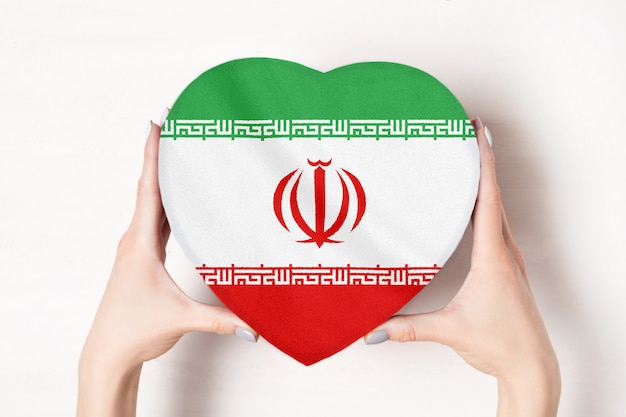 Flag of iran on a heart shaped box in a female hands Premium Photo