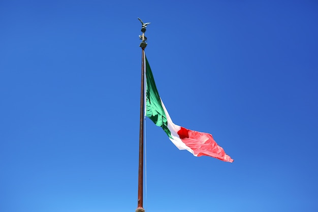 Flag of italy on a blue sky background. symbol of italy Premium Photo