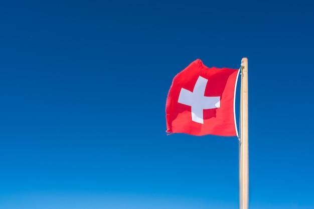 青い空を背景にスイス連邦共和国の旗。 Premium写真