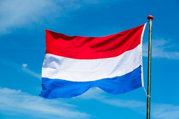 青い空を背景に風になびかせてオランダの旗 Premium写真