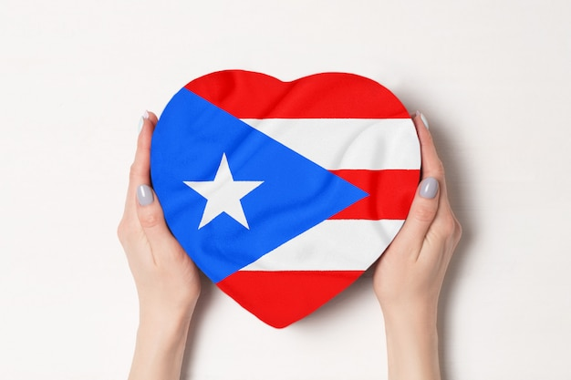 Flag of puerto rico on a heart shaped box in a female hands Premium Photo