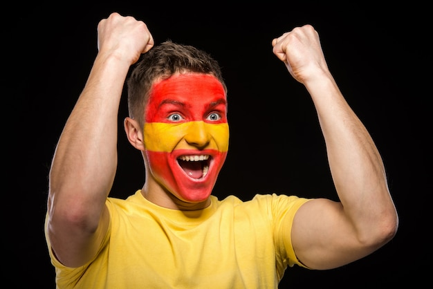 Flag of spain painted on a face man. Premium Photo
