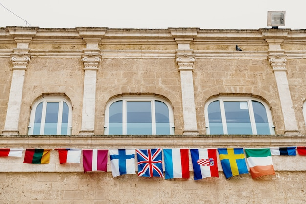 Flags of european countries hanging from a balcony in the italian city of matera. Premium Photo