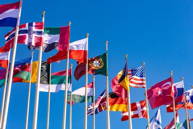 さまざまな国の旗が水色の空を背景に風になびく Premium写真