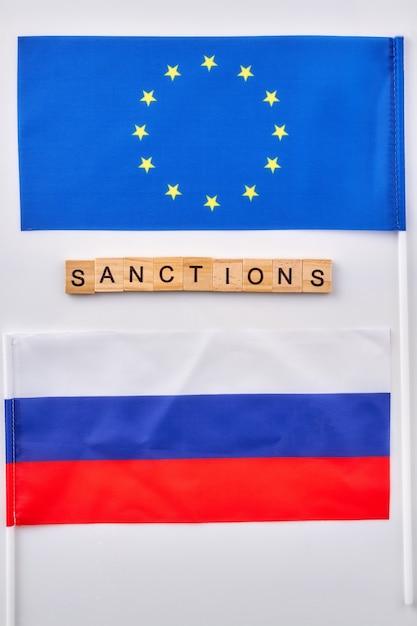 ロシアと欧州連合の旗。木製の立方体で作られた言葉による制裁。 Premium写真
