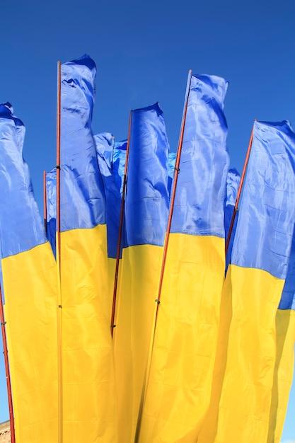 Flags of ukraine waving in the wind against deep blue sky. Premium Photo