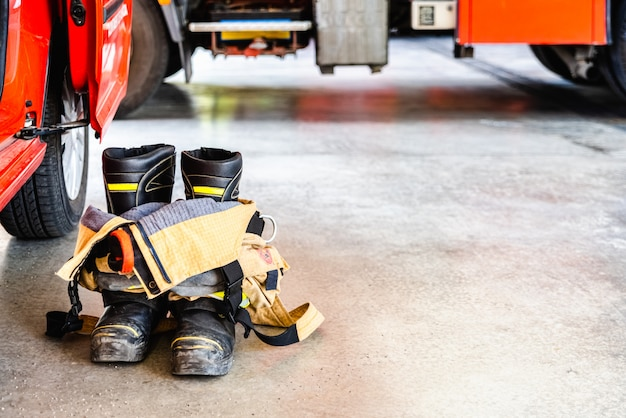Flame retardant fireman's boots and pants ready to be used in case of emergency. Premium Photo