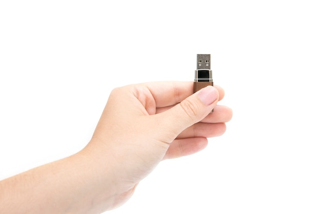 Flash drive in woman's hand on white background. female's hand holding flash drive. Premium Photo
