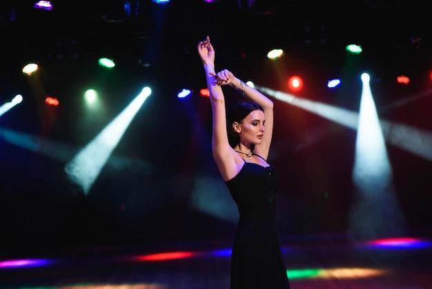 Молодая женщина с удовольствием, схожу с ума в одиночку, яркий сексуальный макияж, веселые вечеринки, ночной образ с flash. Premium Фотографии