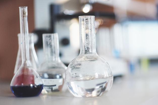 青紫ピンクの液体実験室のコルクが入ったフラスコが、実験室の流体試験のテーブルの上に立っています。 無料写真