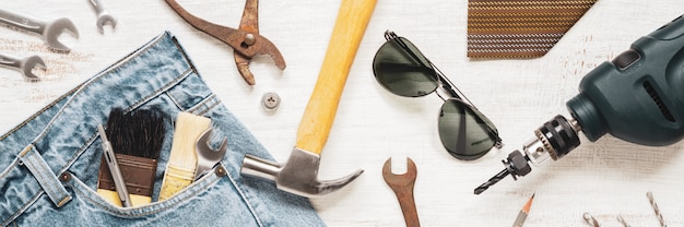 Flat lay accessories tools and clothing for worker on rusty white wooden for web banner. top view for labor or labour day, worker's day, father's day and home diy repair web banner concept. Premium Photo