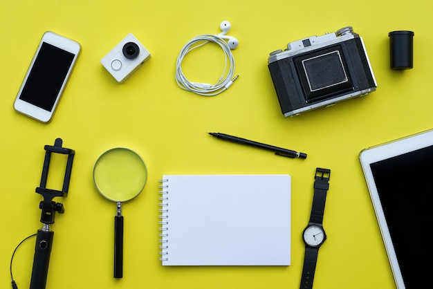 Flat lay of accessories on yellow desk background Premium Photo