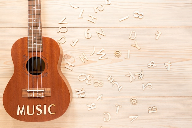 Flat lay acoustic guitar with wooden letters Free Photo