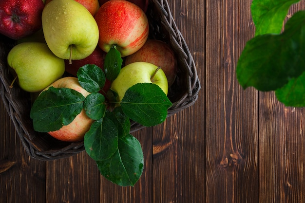 Flat lay apples in box with leaves on wooden background. horizontal space for text Free Photo