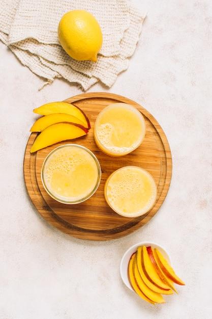 Flat lay arrangement of fresh smoothies next to sliced mango Free Photo