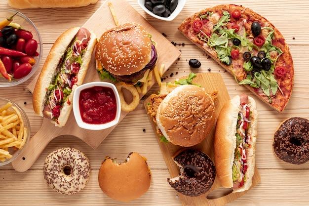 Плоская композиция с гамбургерами и пиццей Premium Фотографии