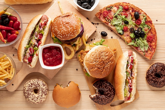 Flat lay arrangement with burgers and pizza Free Photo