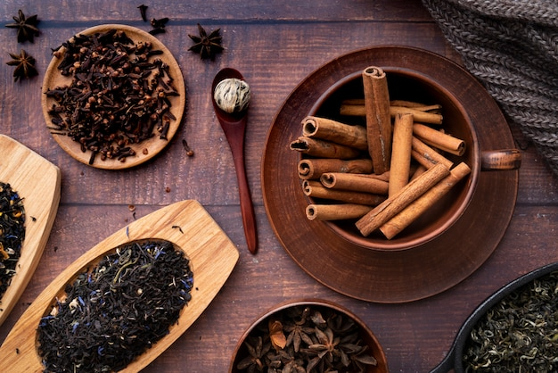 Flat lay arrangement with cinnamon sticks on wooden background Free Photo