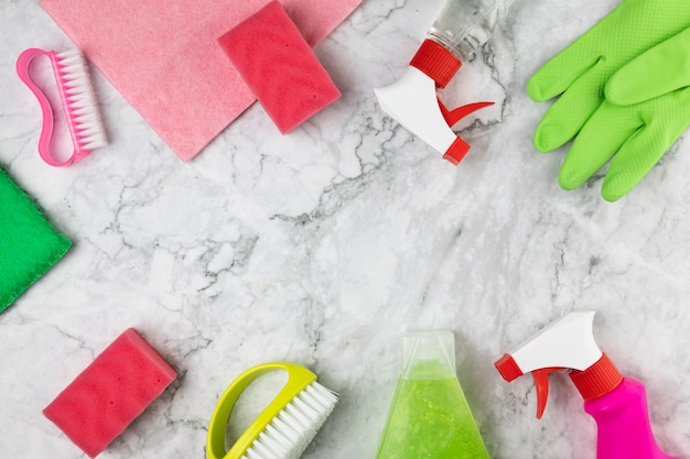 Flat lay arrangement with cleaning items and marble table Free Photo