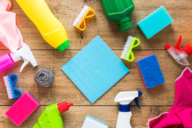 Flat lay arrangement with cleaning products and wooden background Free Photo