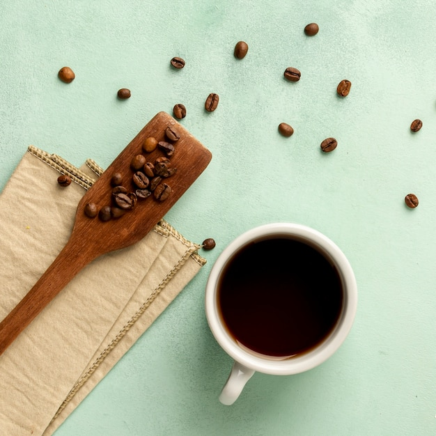 Flat lay arrangement with coffee cup and beans Free Photo