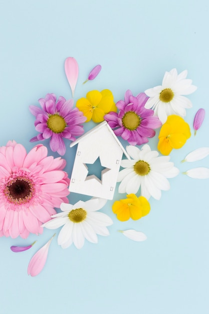 Flat lay arrangement with flowers and wooden house Free Photo