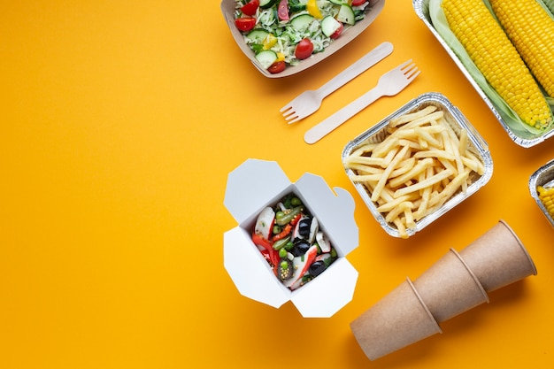 Flat lay arrangement with fries, salad and corn Free Photo