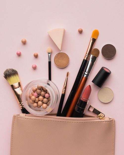 Flat lay arrangement with make-up products with beauty bag Free Photo