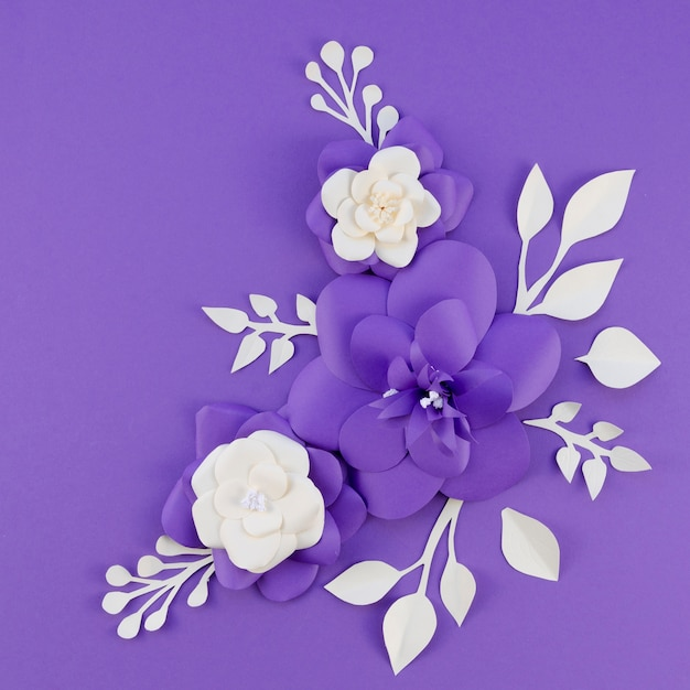 Flat lay arrangement with paper flowers on purple background Free Photo