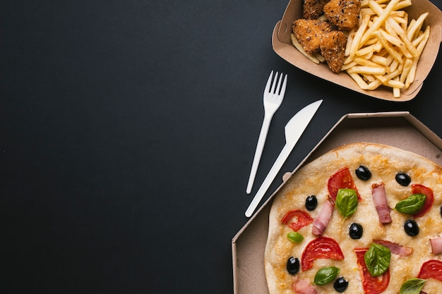 Flat lay arrangement with pizza and fast food Free Photo