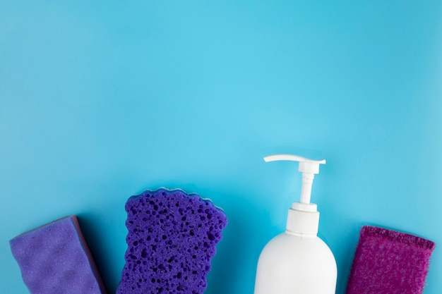Flat lay arrangement with purple sponges and soap bottle Free Photo
