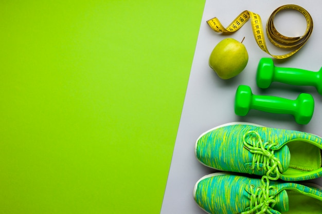 Flat lay arrangement with running shoes and dumbbells Premium Photo