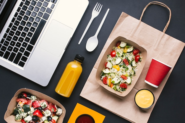 Flat lay arrangement with salad and laptop Free Photo