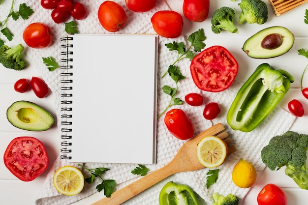 Flat lay arrangement with vegetables and notebook Free Photo