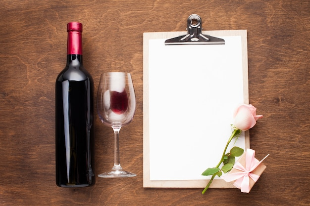 Flat lay arrangement with wine and clipboard Free Photo