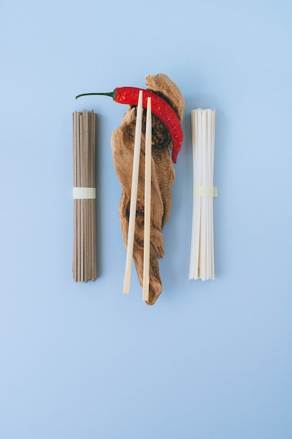 Flat lay asian noodles, red chili, chopsticks on wooden sticks on a bright blue background Premium Photo