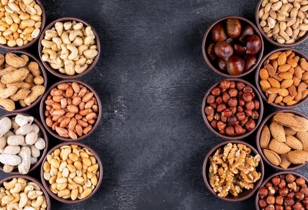 Piatto disteso noci assortite e frutta secca in mini ciotole diverse con noci pecan, pistacchi, mandorle, arachidi Foto Gratuite