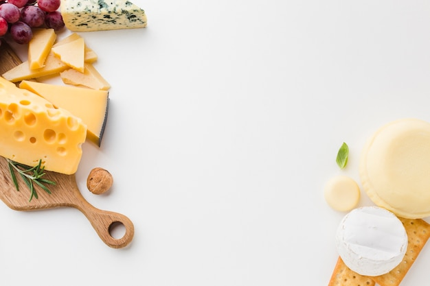 Flat lay assortment of cheese on wooden cutting board Free Photo